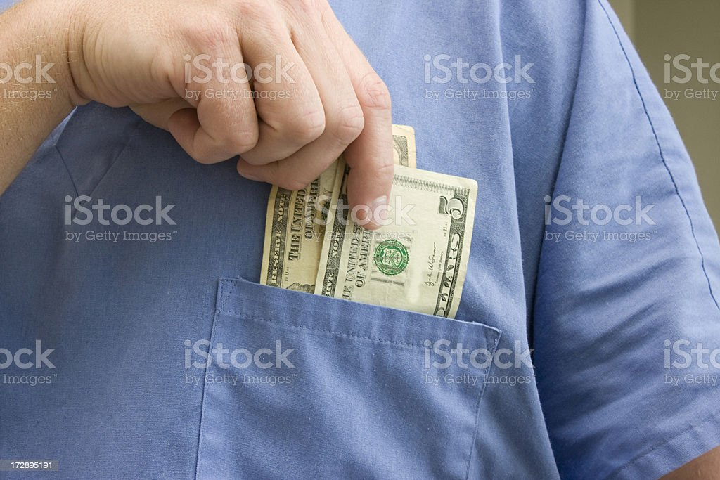 Doctor placing money in his pocket royalty-free stock photo