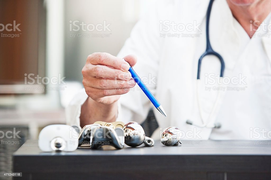 Doctor pointing at different kinds of arthroplasties stock photo