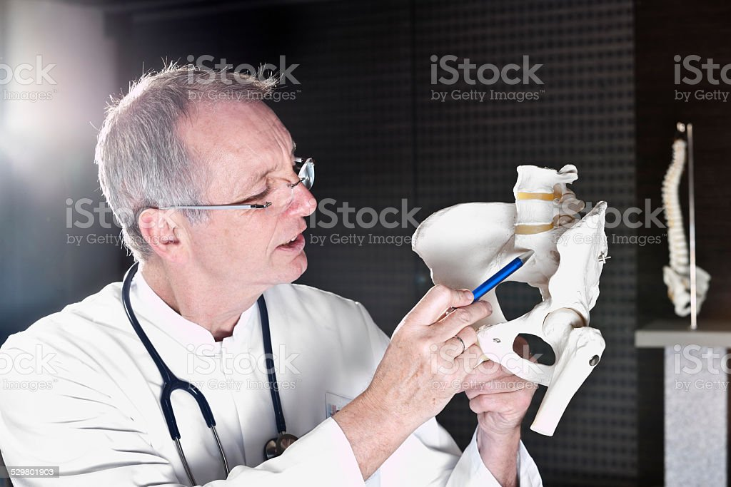 Doctor pointing at sacrum stock photo