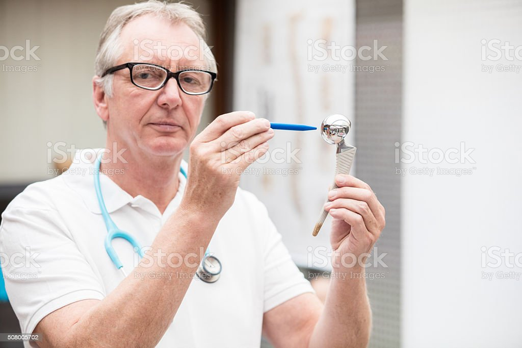 Doctor pointing at total hip endoprothesis stock photo