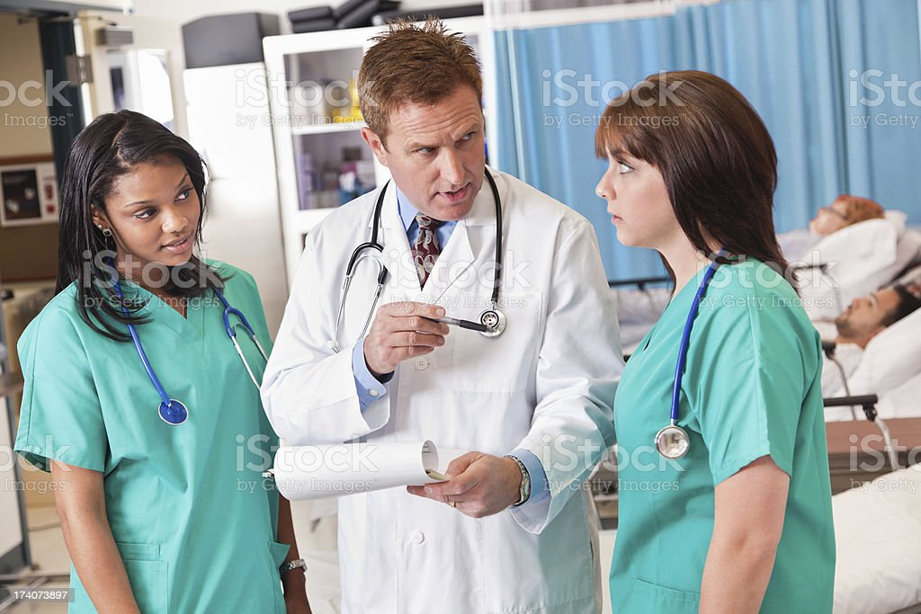 Doctor pointing to nurse discussing procedures in hospital recovery room stock photo