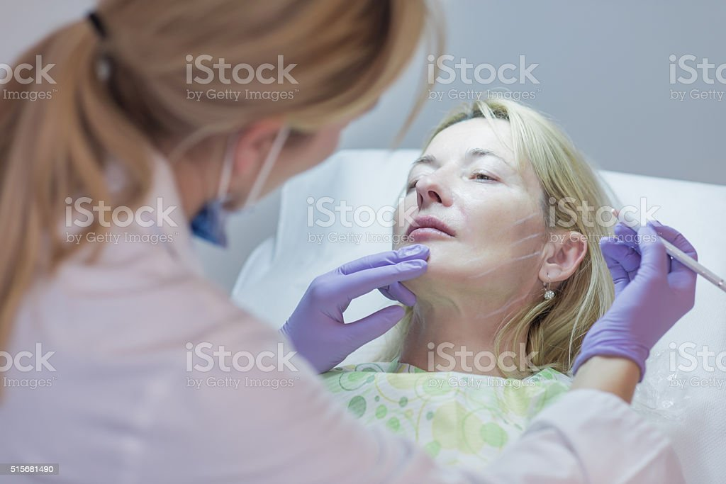 Doctor preparing mature woman for botox injection stock photo