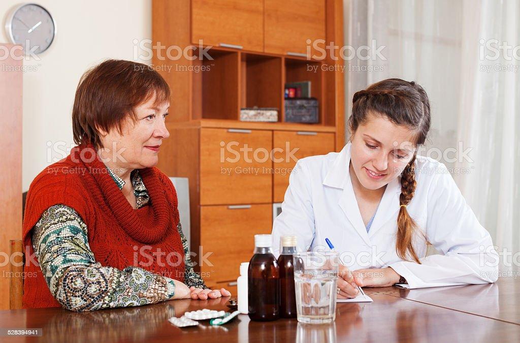 doctor prescribing medication to senior woman stock photo
