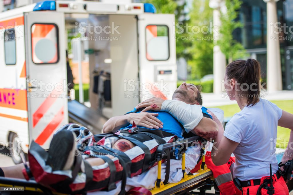 Female doctor providing first aid to man injured in car accident.