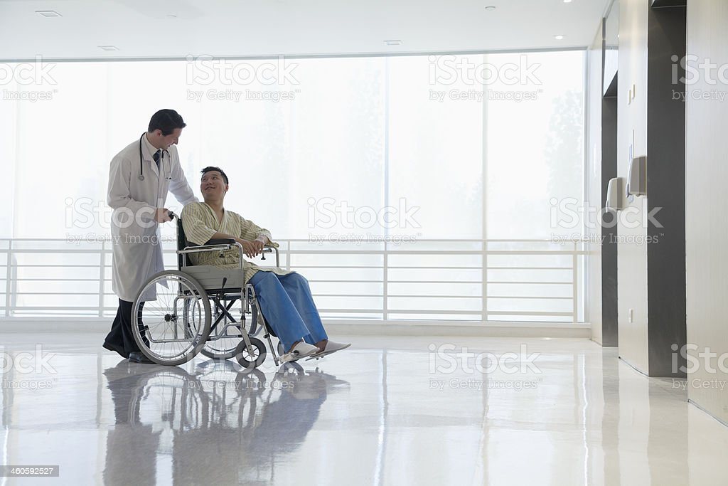 Doctor pushing and assisting patient in the hospital, Beijing, China stock photo
