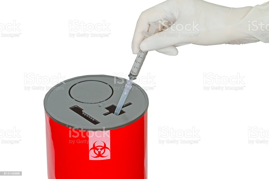 Doctor put syringe in red disposal boxes on white stock photo