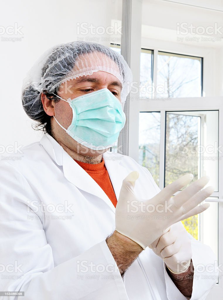 Doctor putting on disposable gloves stock photo
