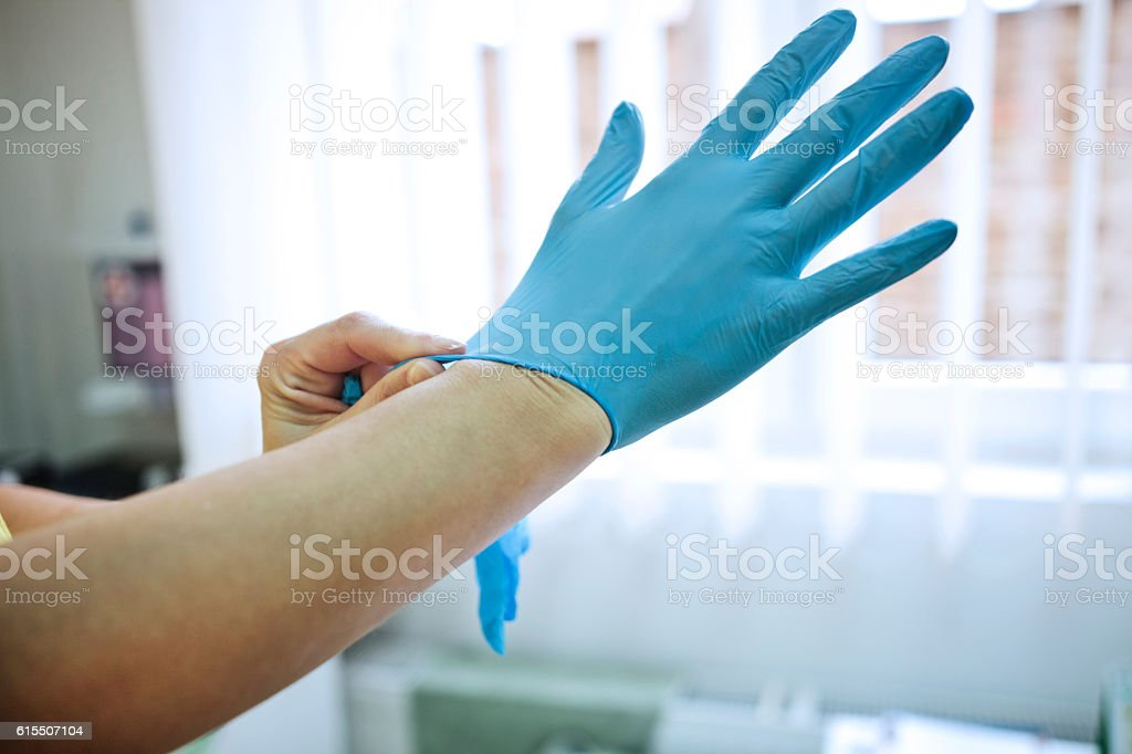 Doctor putting on medical gloves stock photo