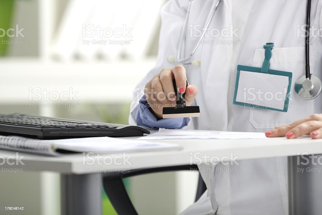doctor putting stamp on a document royalty-free stock photo