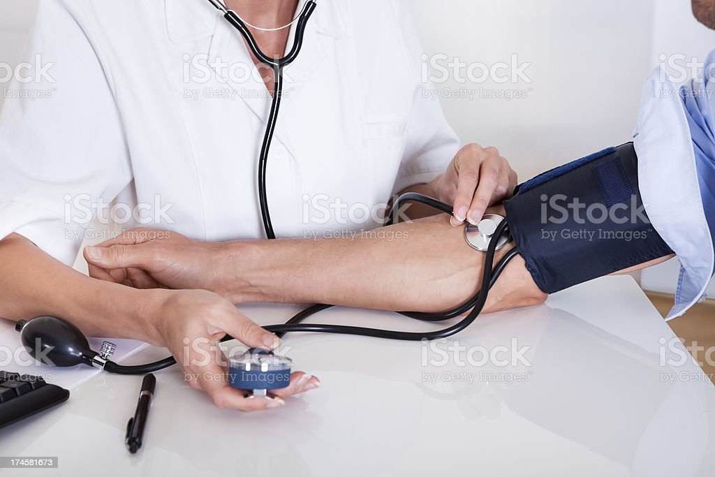 A doctor reading a patients blood pressure stock photo