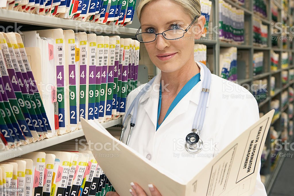 Doctor reading medical records stock photo
