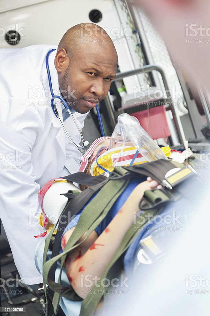 Doctor receiving injured victim from ambulance stock photo