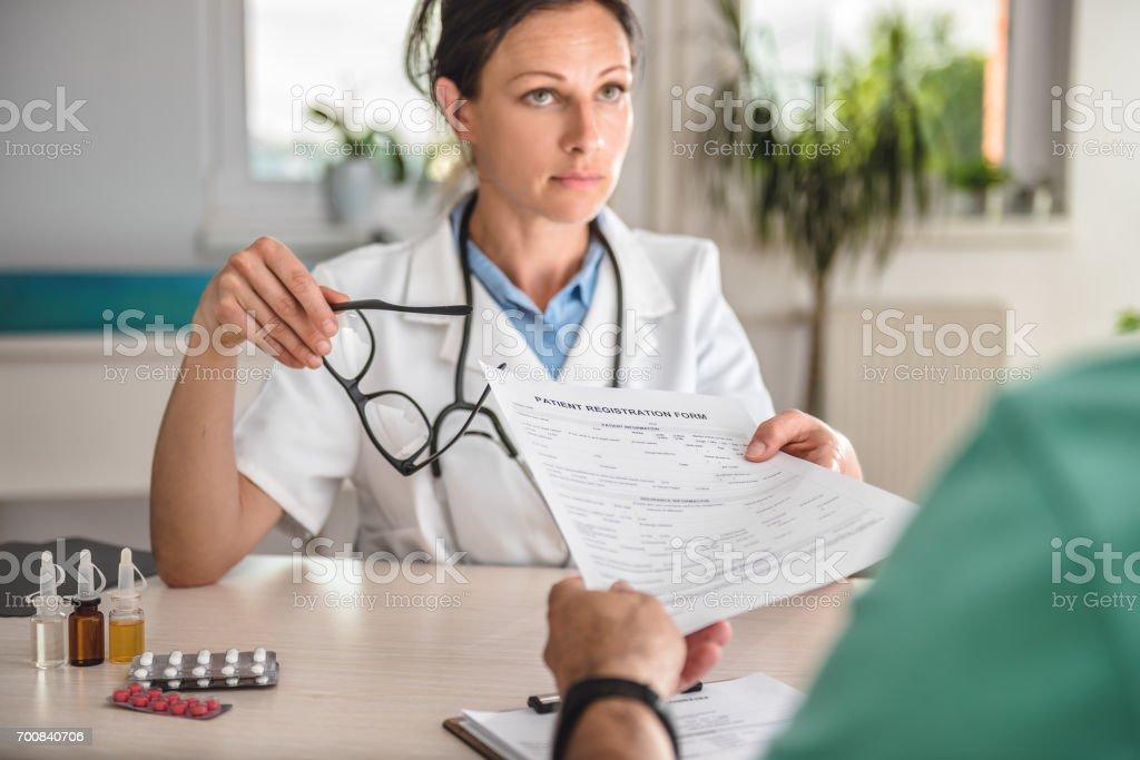Doctor receiving patient registration form in hospital