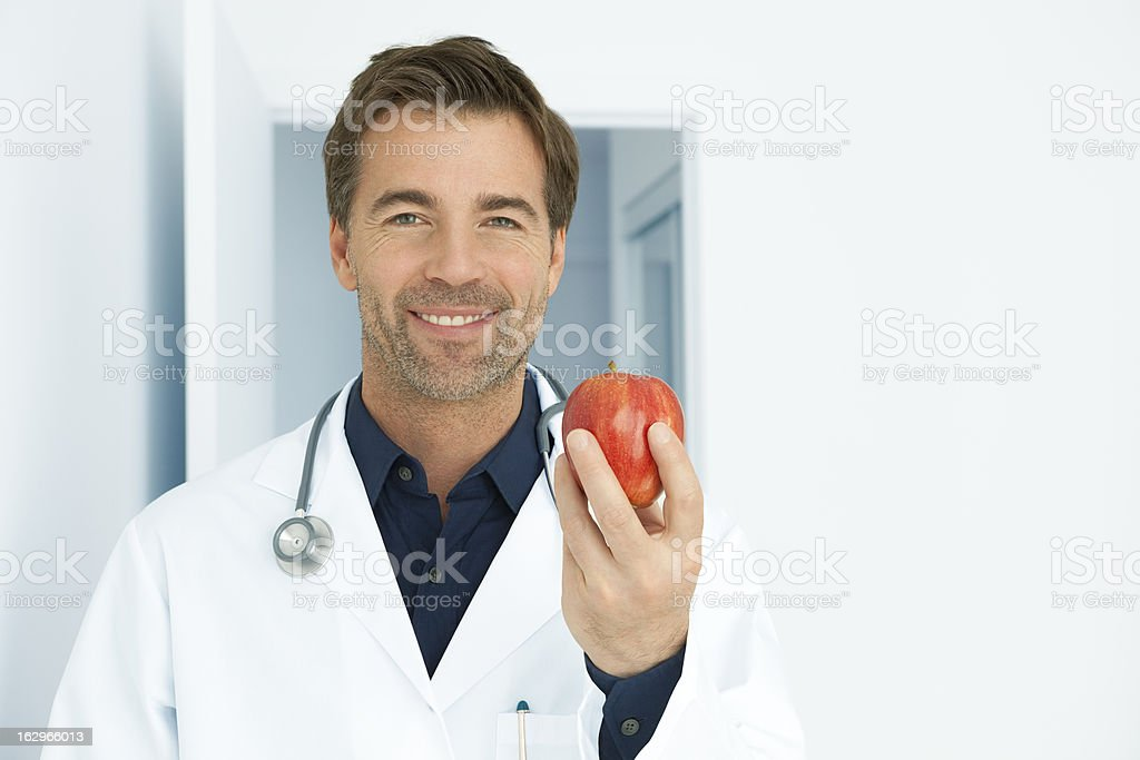 Doctor Recommending An Apple A Day royalty-free stock photo