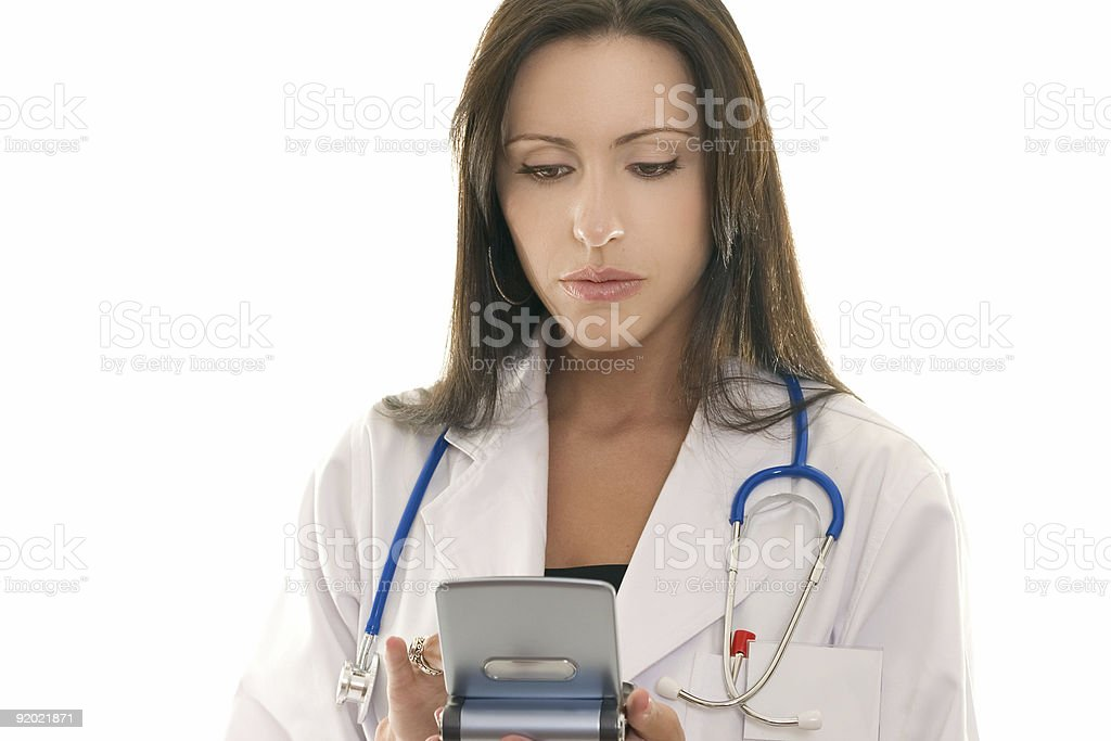 Doctor referencing information on a portable device royalty-free stock photo