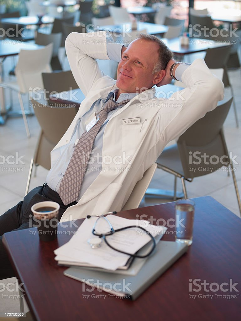 Doctor relaxing in cafeteria stock photo