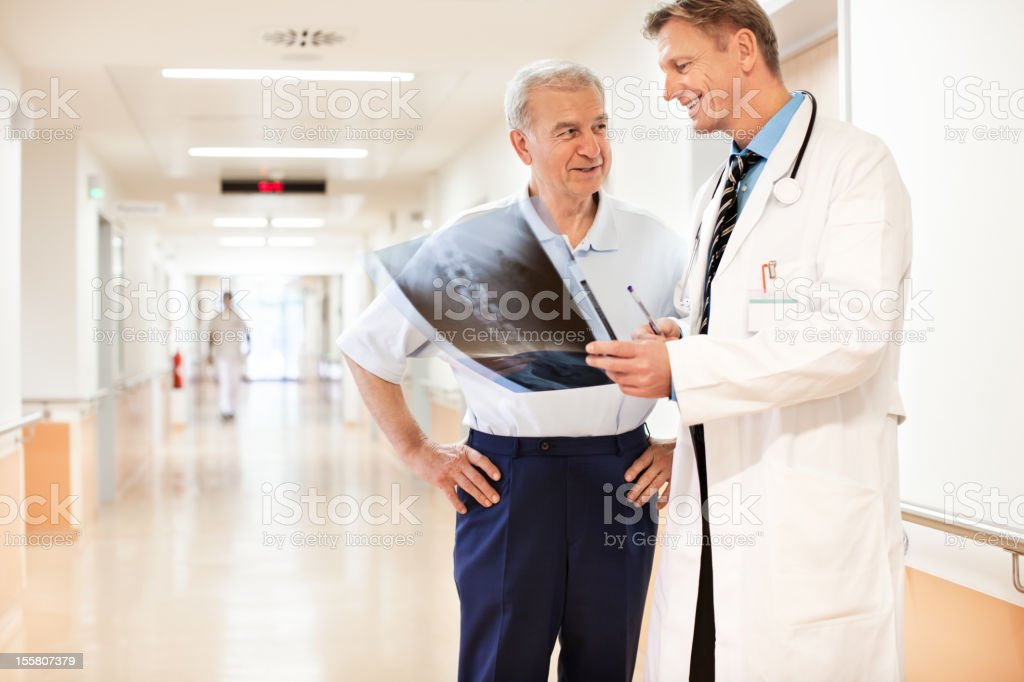 Doctor reviewing an x-ray image with patient stock photo