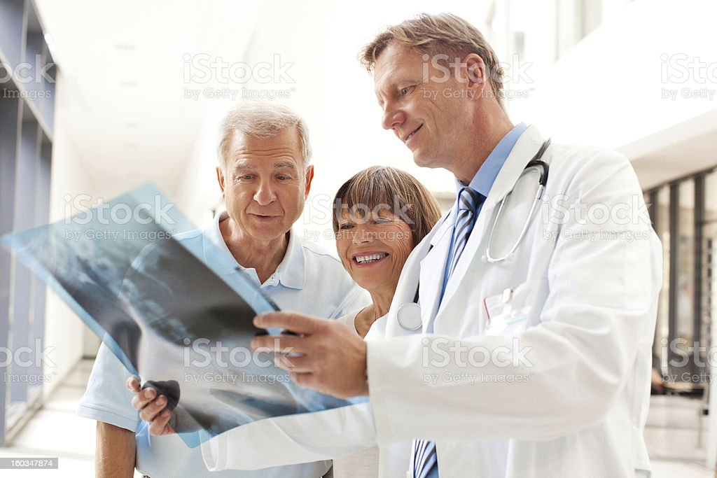 Doctor reviewing an x-ray image with patients stock photo