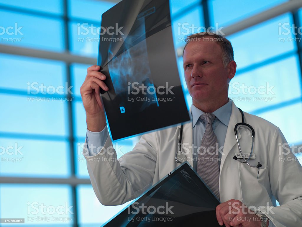 Doctor reviewing x-rays royalty-free stock photo