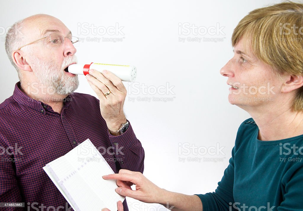 Doctor reviews patient's lung capacity with a peak flow meter stock photo