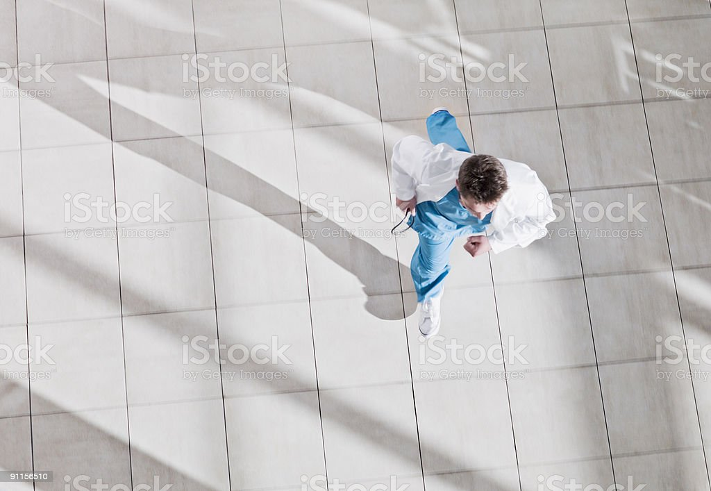 Doctor running through hospital lobby royalty-free stock photo