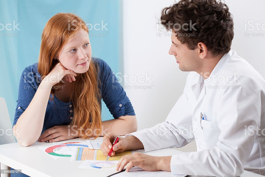 Doctor selecting contraception for girl stock photo