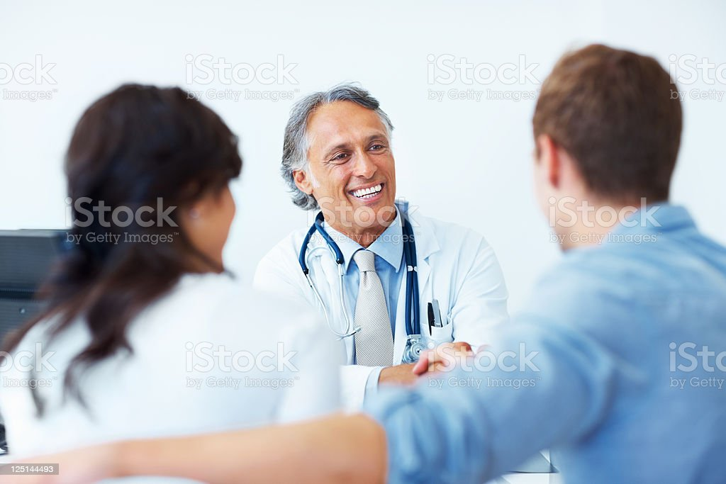 Doctor shaking hands with the patients stock photo