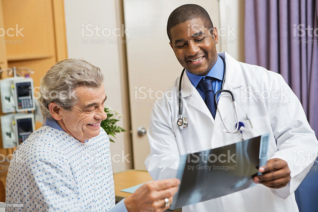 Doctor sharing information to patient while looking at his x-ray royalty-free stock photo