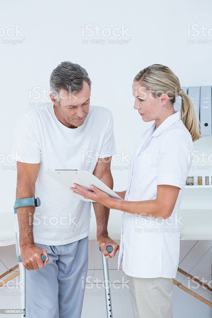 Doctor showing clipboard to her patient with crutch stock photo