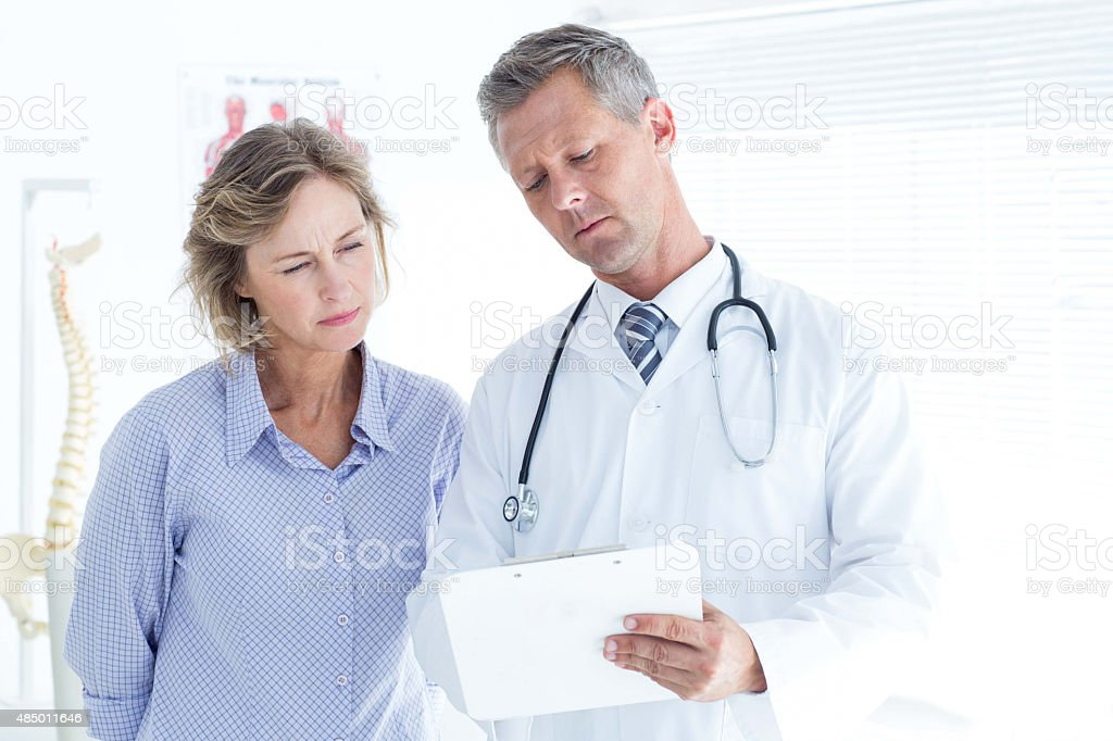 Doctor showing his notes to patient stock photo