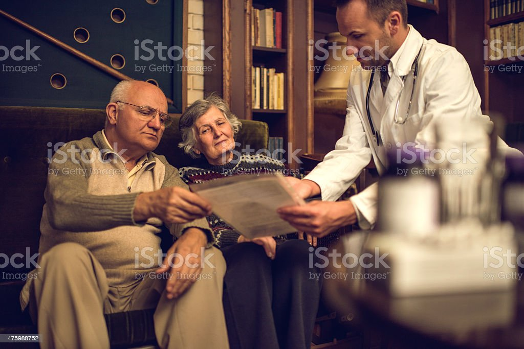 Doctor showing medical documents to a senior couple at home. stock photo