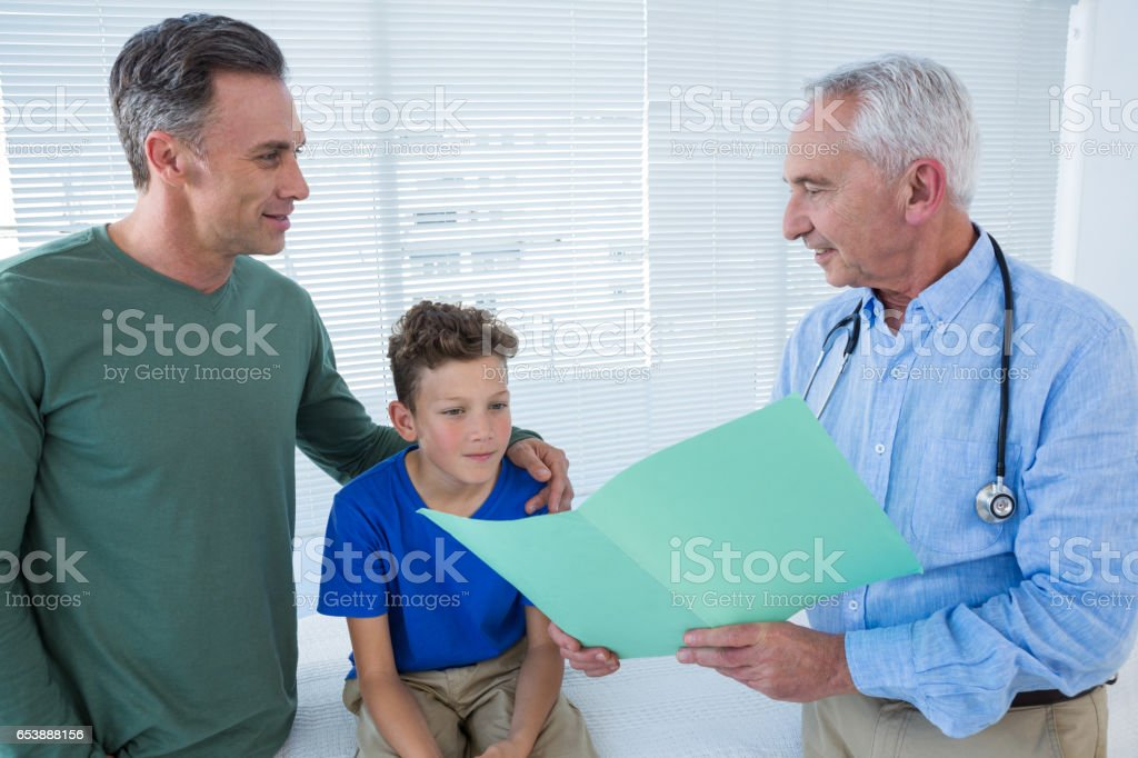 Doctor showing medical report to patient and his parent stock photo