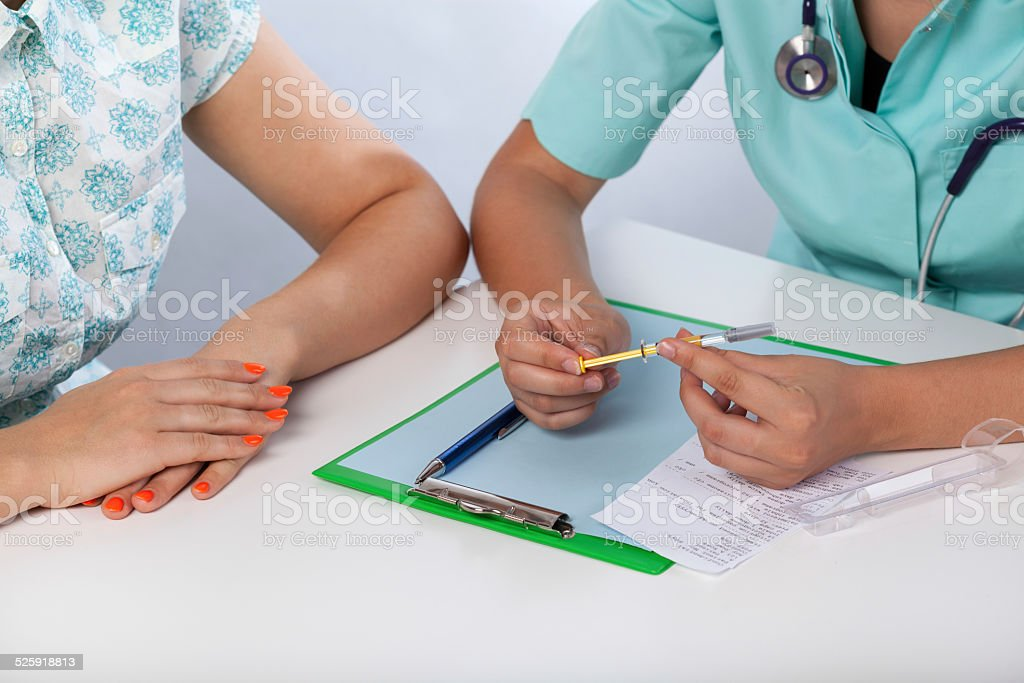 Doctor showing patient a syringe stock photo