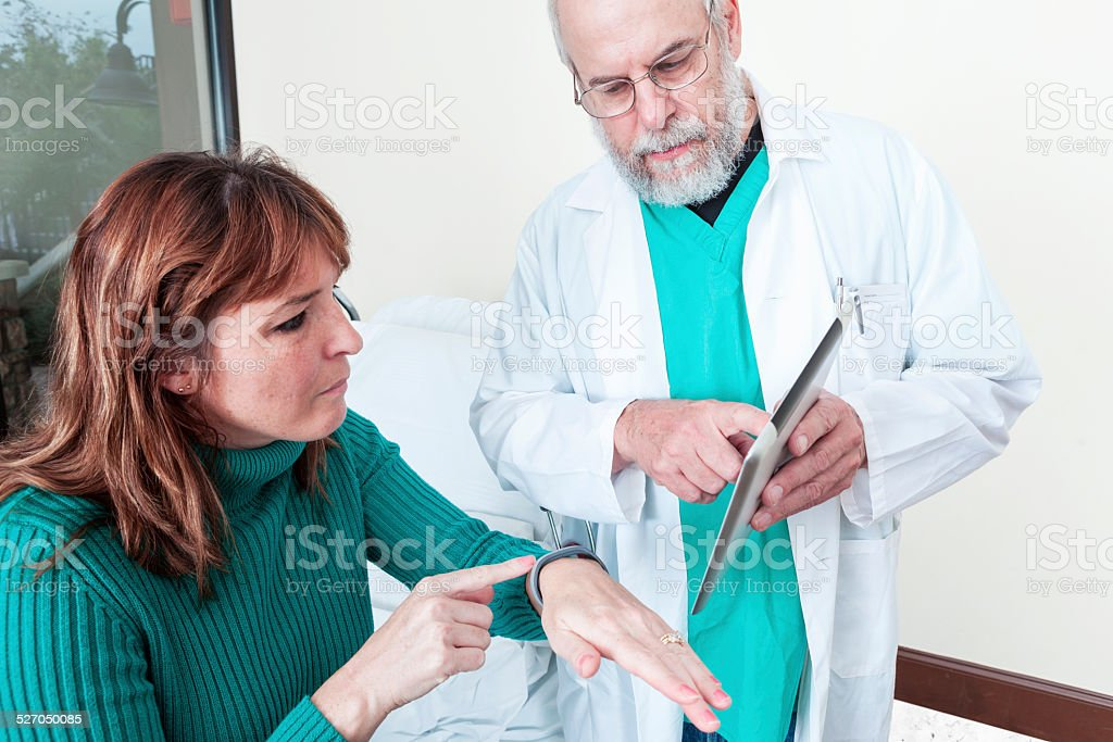 Doctor Showing Patient Smart Device to Monitor Her Health stock photo