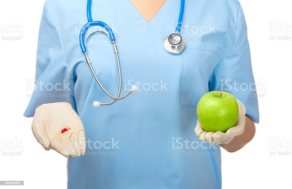 Doctor showing pill and green apple royalty-free stock photo