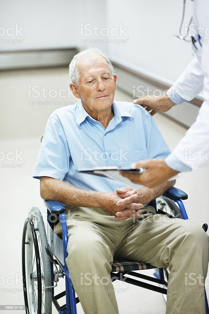 Doctor showing reports to a disabled man royalty-free stock photo