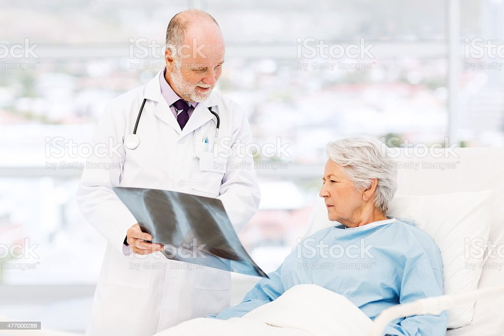 Doctor Showing X-Ray To Patient In Hospital stock photo