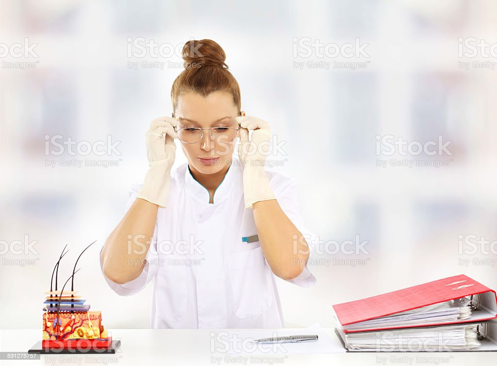 Doctor sitting at the desk with eyeglasses in her hands stock photo