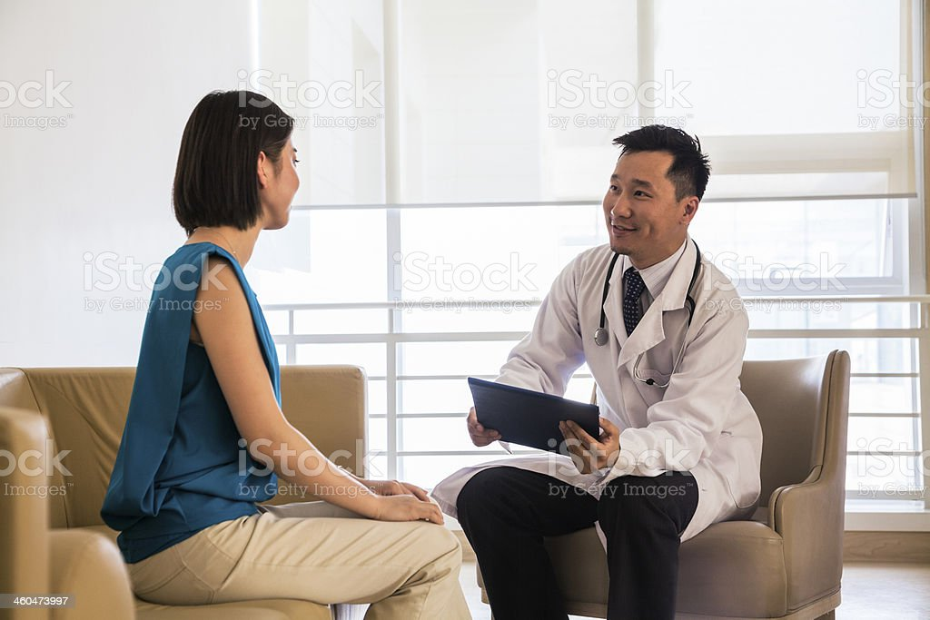 Doctor sitting down and consulting patient in the hospital stock photo