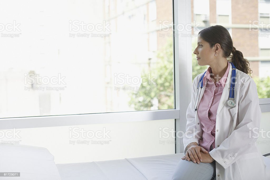 Doctor sitting in hospital room looking out large windows royalty-free stock photo