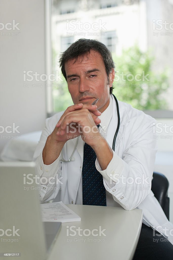 Doctor sitting in office with laptop  stock photo