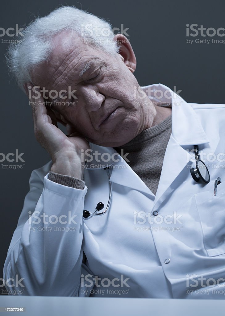 Doctor sleeping at the desk stock photo