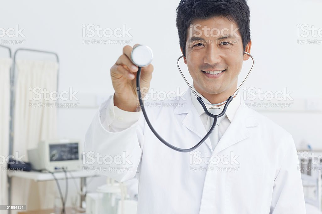 Doctor smiling as he holds the base of a stethoscope stock photo