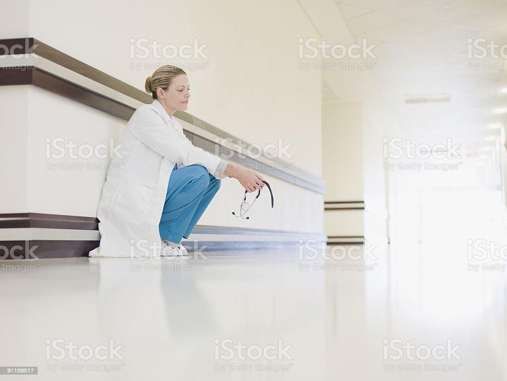 Doctor squatting in hospital corridor royalty-free stock photo