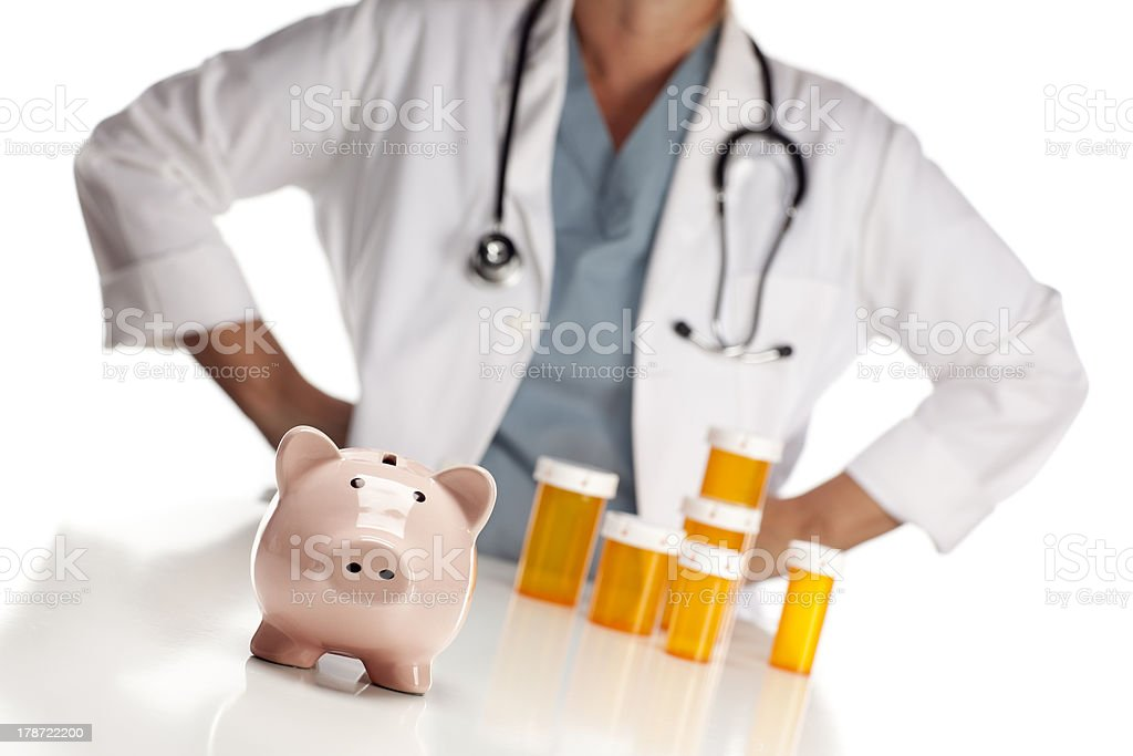 Doctor Standing Behind Medicine Bottles and Piggy Bank stock photo