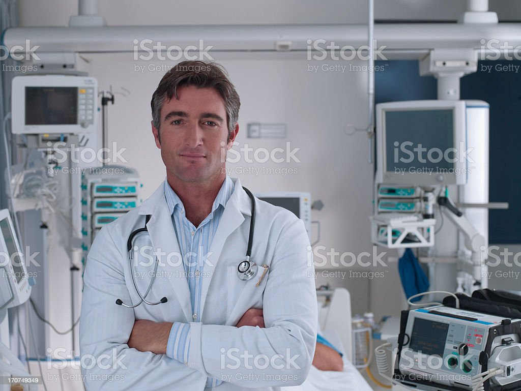 Doctor standing in hospital intensive care with arm closed stock photo