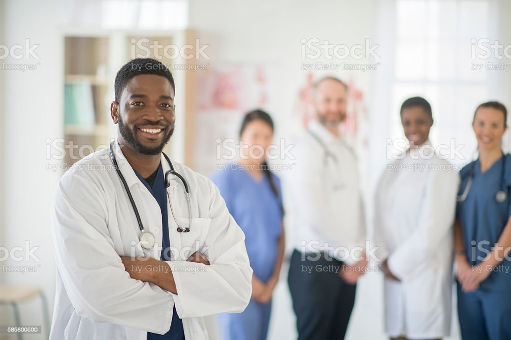 Doctor Standing with His Medical Team stock photo