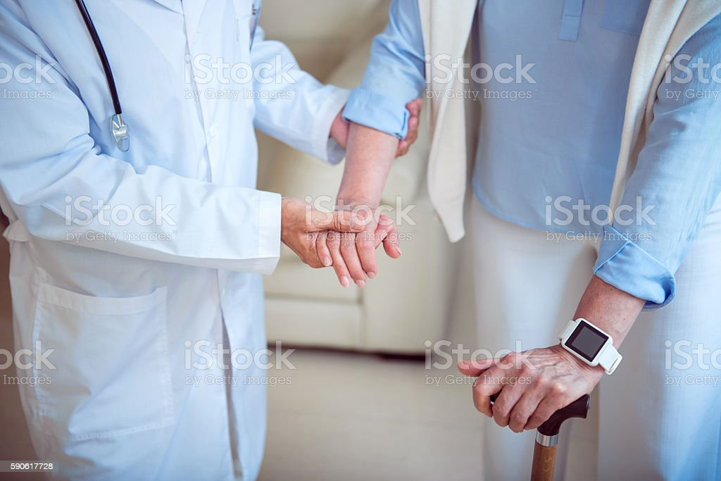 Doctor supporting female patient stock photo