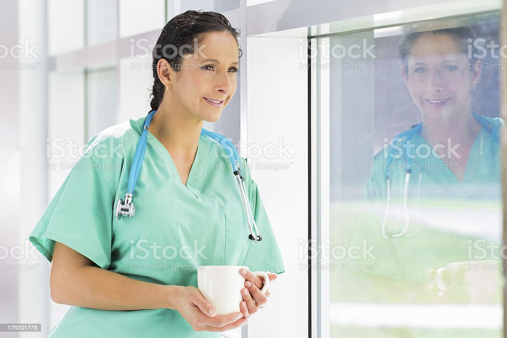 Doctor taking a coffee break looking out the window royalty-free stock photo