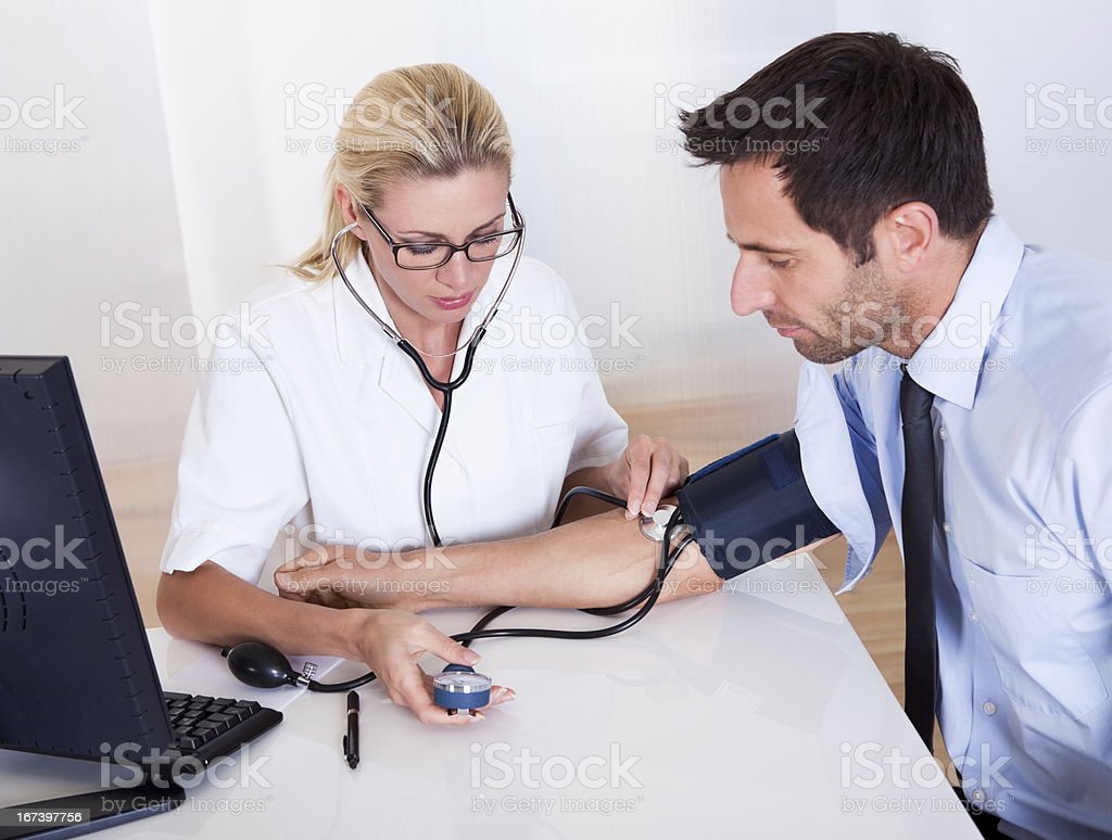 Doctor taking a patients blood pressure royalty-free stock photo